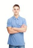 Der lächelnde Mann, der mit den Händen steht, faltete sich gegen lokalisiert auf Weiß Lizenzfreies Stockfoto