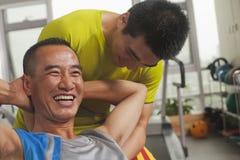 Der lächelnde Mann, der mit seinem Trainer ausarbeitet, tuend sitzen ups Stockbilder