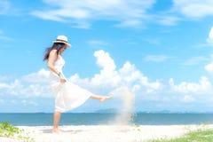 Der lächelnde weiße tragende Modesommer der asiatischen Frau, der auf den sandigen Ozean geht, setzen auf den Strand Frau genieße stockfotos