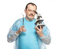 Der lächerliche fette Chirurg mit einer Zigarette und einem Mikroskop Lizenzfreies Stockfoto