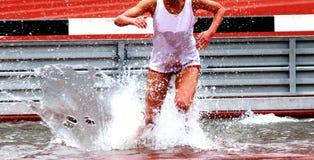 Der Läufer, der im Hindernisrennen konkurriert, landet im Wasser lizenzfreie stockfotos