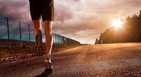 Der Läufer in Sonnenuntergang und in Erfolg stockbilder