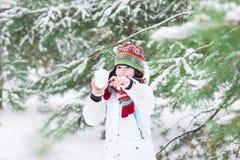 Der lachende Junge, der Schneeball spielt, kämpfen im schneebedeckten Vorderteil Lizenzfreie Stockbilder