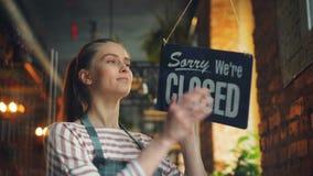 Der Ladenbesitzer, der tut mir leid sind uns hängt, geschlossenes Zeichen auf Haustür lächelnd, Außenseite schauend stock footage