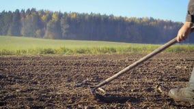 Der Landwirt behandelt das Land mit einer Hacke stock video footage
