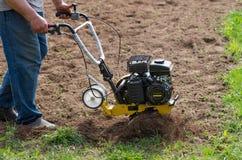 Der Landwirt pflügt das Land mit einem motoblock Der Landwirt löst den Boden stockbild
