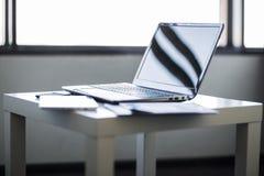 der Laptop an dem Arbeitsplatz Lizenzfreie Stockbilder