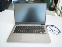 Der Laptop und die Gläser setzten sich auf dem Tisch stockfotografie