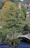 Der laufende Gedanke des Flusses die Mitte der Stadt von hebden Brücke mit Hausmühlkaminen und der historischen Steinbrücke Lizenzfreie Stockfotos