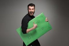 Der lächelnde Mann als Geschäftsmann mit grüner Platte Stockfotos