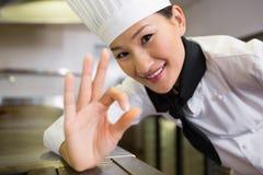 Der lächelnde weibliche Koch, der o.k. gestikuliert, unterzeichnen herein Küche Lizenzfreies Stockfoto