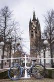 Der lehnende Turm der alten Kirche in Delft In der Front ein Fahrrad, das am Geländer von sich lehnt stockfotos