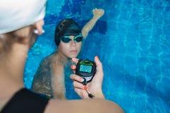 Der Lehrer im Pool mit einer Stoppuhr markiert die Zeit am Th stockbild
