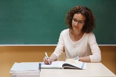Der Lehrer sitzt am Schreibtisch und überprüft Schulnotizbücher Stockfotos