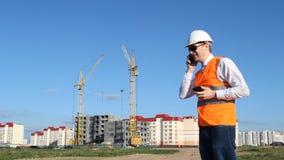 Der Leiter, den der Inspektor an zwei Telefonen vor dem hintergrund des Bauens eines Hauses spricht stock video footage