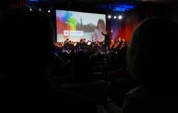 Der Leiter, der Sinfonieorchester mit Ausführenden auf Hintergrund während der Eröffnungsfeier des Geschäfts verweist, blutete st Lizenzfreies Stockfoto