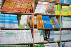Der lernenden Studenten und die Unterrichtungsbücher werden in den Buchhandlungen verkauft Lizenzfreie Stockbilder