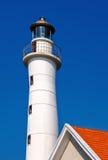 Der Leuchtturm und die Spitze des roten Dachs mit hellem Himmel Lizenzfreie Stockfotografie