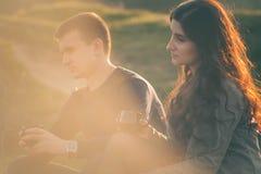Der liebevollen jungen Paare glücklicher zusammen, trinkender Tee im Freien Ein Kerl mit einem Mädchen auf dem See bei Sonnenunte Lizenzfreie Stockfotos