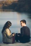 Der liebevollen jungen Paare glücklicher zusammen, trinkender Tee im Freien Ein Kerl mit einem Mädchen auf dem See bei Sonnenunte Lizenzfreie Stockbilder