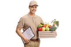Der Lieferer, der eine Kiste hält, füllte mit Lebensmittelgeschäften und Klemmbrett lizenzfreie stockfotografie