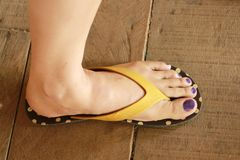 Der linke Fuß der Frau trug Sandalen stehen auf dem Bretterboden Stockfotos