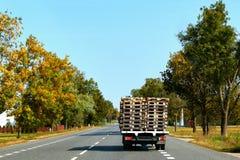 Der LKW oder der Lastwagen geht die Landstraße mit hölzerner Palette weiter lizenzfreie stockfotografie