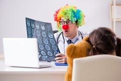 Der lustige Kinderarzt mit kleinem Mädchen an der regelmäßigen Überprüfung stockbild