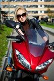 Der Mädchen blonde sg auf rotem Motorrad Lizenzfreie Stockbilder
