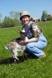 Der Mädchen-Landwirt und die junge Ziege. stockfoto