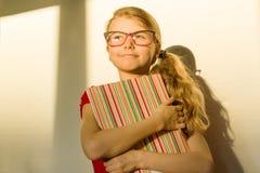 Der Mädchenkindergrundschüler, der Gläser trägt, hält ein Lehrbuch und träumerisch lächelndes vorwärts schauen stockbild