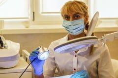 Der Mädchenkosmetiker leitet das Verfahren im Schönheitssalon doktor lizenzfreies stockfoto