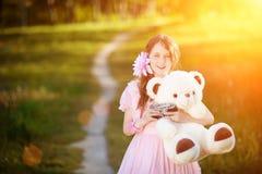 Der Mädchenphotograph in einem rosa Kleid, das ein Teddybär bearin die Strahlen eines hellen Sonnenscheins umarmt Lizenzfreie Stockfotos