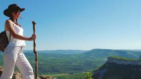 Der Mädchenreisende in einem Cowboyhut und weißen einer Kleidung steht auf die Oberseite des Berges und bewundert die erstaunlich stock video