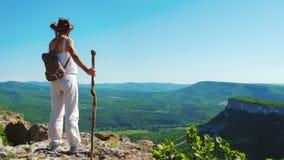 Der Mädchenreisende in einem Cowboyhut und weißen einer Kleidung steht auf die Oberseite des Berges und bewundert die erstaunlich stock footage