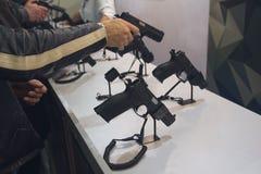 Der Männer wählen Gewehre auf Ständen mit stockfoto