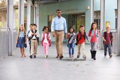 Der männliche Lehrer, der in Korridor mit Volksschule geht, scherzt lizenzfreie stockfotos