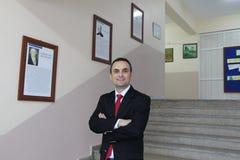 Der männliche Lehrer im Schulkorridor Lizenzfreies Stockfoto