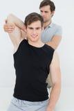 Der männliche Physiotherapeut, der ein Lächeln jung ausdehnt, bemannt Arm Stockbilder