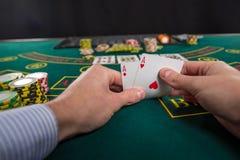 Der männliche Pokerspieler, der die Ecken von zwei Karten anhebt, schafft mit links Stockfotografie