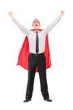 Der männliche Superheld, der seins anhebt, teilt von der Freude aus Stockfoto
