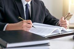 Der männlicher Rechtsanwalt oder Richter, die mit Gesetzbüchern, Hammer arbeiten, berichten über das c lizenzfreies stockfoto