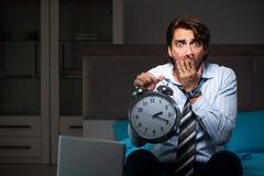 Der müde Geschäftsmann über die Zeit hinaus, der zu Hause nachts arbeitet stockbild