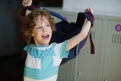 Der müde kleine Student, der in der Halle nahe den Schließfächern steht und trägt einen Rucksack Stockfoto