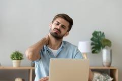 Der müde Mann, der am Schreibtisch sitzt, hat Nackenschmerzen lizenzfreies stockfoto