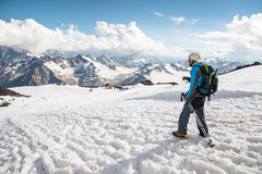Der müde Reisende steigt von der schneebedeckten Spitze vor dem hintergrund der Schnee-mit einer Kappe bedeckten Berge ab stockbilder