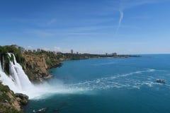 Der 40m hohe Duden-Wasserfall und kleine Boot im Ozean Lizenzfreie Stockfotos