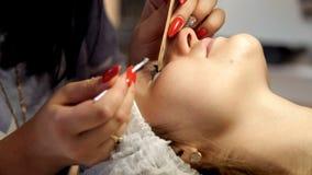 Der Make-upkünstler bereitet den Kunden für Wimpererweiterungen vor und entfernt alte Wimpern stock footage
