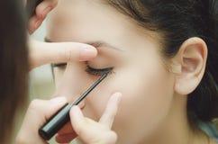 Der Make-upmeister malt die Augen des Mädchens Macht Make-up, Nahaufnahme stockfotos