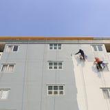 Der Maler benutzt eine Farbenrolle außerhalb des hohen Gebäudes Stockfotos